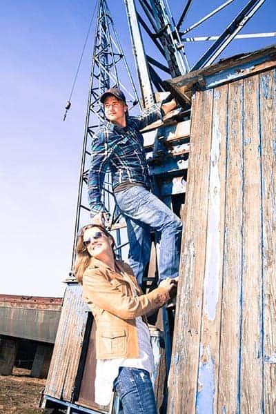 Pärchen mit coolen Klamotten klettert einen alten Kran hinauf