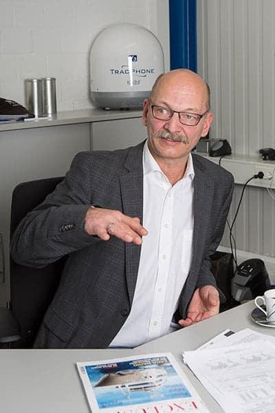 Unternehmer am Schreibtisch gestikuliert