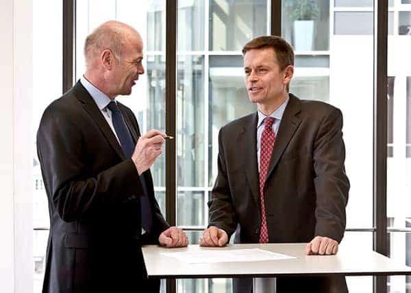 Zwei Manager diskutieren an einem Stehtisch