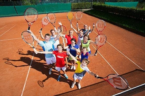 Viele Kinder mit Tennisschlägern stehen jubelnd und lachend auf dem Tennisplatz