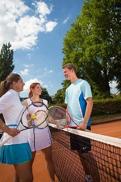 Zwei Frauen und ein Mann mit Tennisschlägern stehen sich am Netz gegenüber
