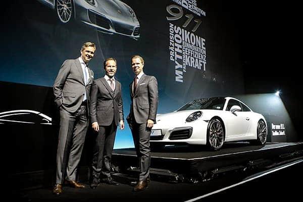 Drei Manager stehen vor dem neuen Porsche 911