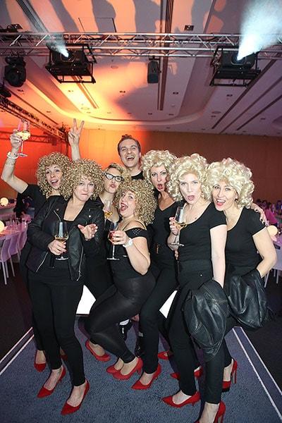 Sieben Frauen mit blonden Lockenperücken und ein Mann feiern