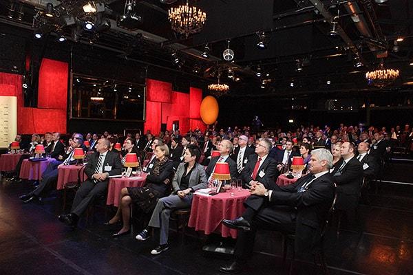 Zuhörer sitzen an kleinen Tischen in einem großen dunklen Saal