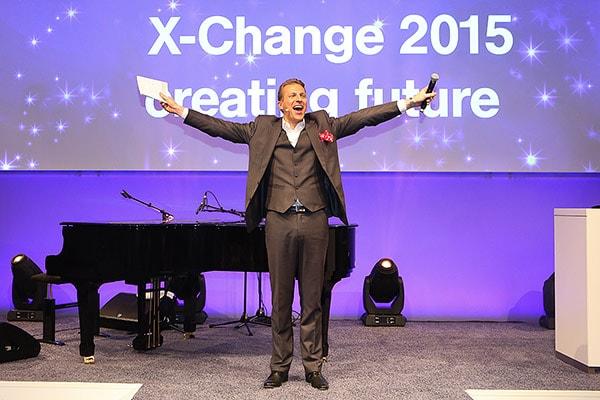 Redner auf einer Bühne breitet die Arme aus