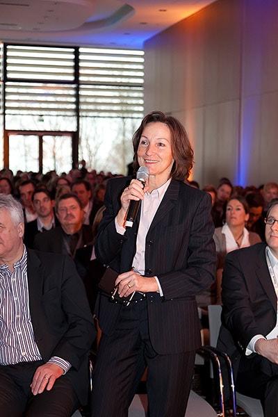 Zuhörerin eines Vortrags stellt eine Zwischenfrage