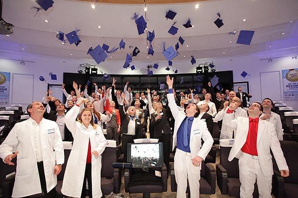 Menschen in weißer Kleidung werfen blaue Hüte in die Luft