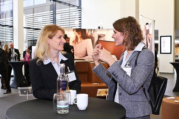 Zwei Frauen unterhalten sich an einem Stehtisch