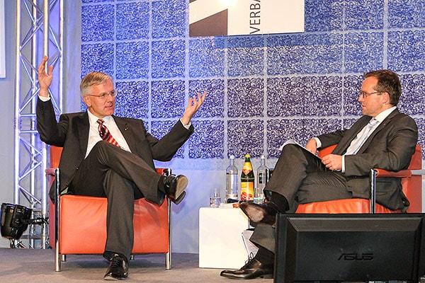 Diskussionsbühne mit zwei Männern auf Ledersesseln