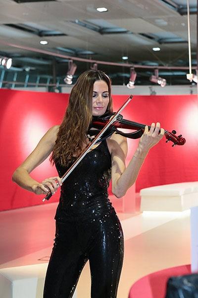 Frau in schwarzen Glitzeranzug spielt Geige